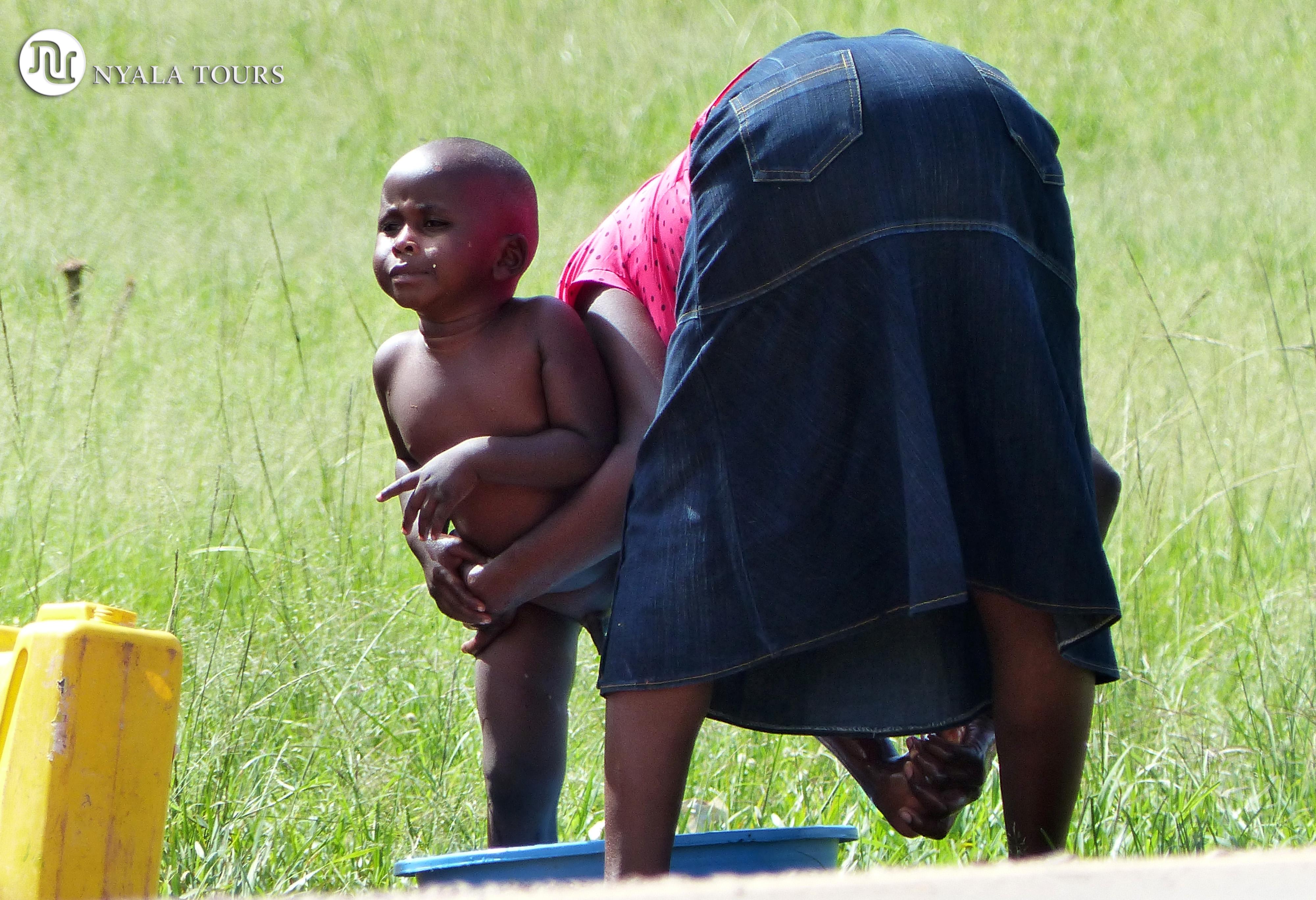 Mom bathing child, Uganda. Mamá bañando a su hijo, Uganda.