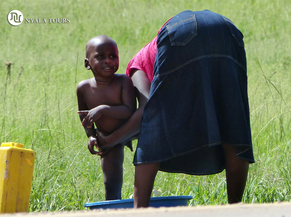 Madre bañando su hijo, por el camino a Kampala.  Mom bathing child on the way to Kampala.
