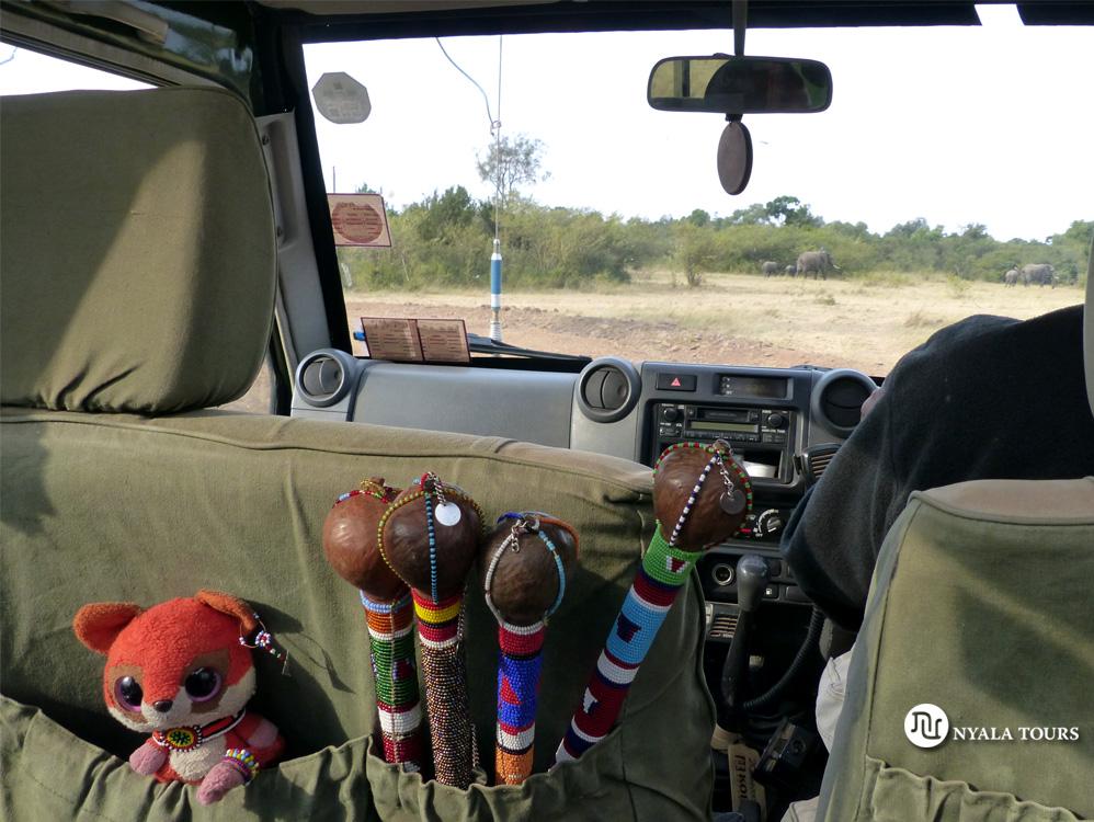 Ruby en su asiento en el 4X4 con bastones Masai (rungu) y vistas de elefantes en el fondo.